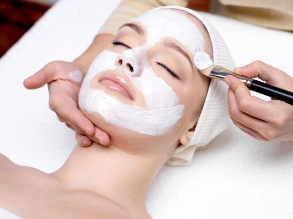 A woman having a customized facial peel applied to her face.